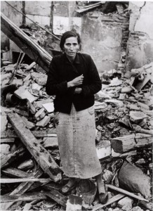 Robert Capa, [Woman standing amid rubble of buildings destroyed by Nationalist air raids, Madrid], Winter 1936/37. The Robert Capa and Cornell Capa Archive, International Center of Photography.