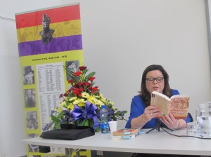 Dawn Purvis reads from They Shall Not Pass. Behind her is the Roll of Honor of Irish participants in the SCW.