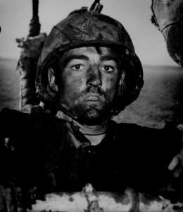 A Coast Guard assault transport comes this Marine after two days and nights of Hell on the beach of Eniwetok in the Marshall Islands. February 1944. US National Archives, Public Domain.