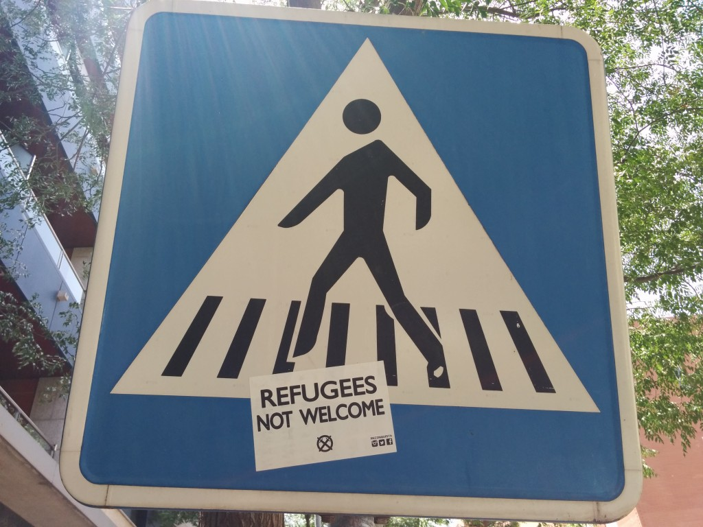 """Refugees Not Welcome"" sticker on a traffic sign in Córdoba, Spain. Photo Rafael Robles. CC BY 2.0"