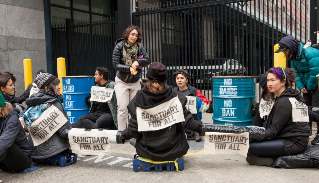 "Protesters with locked arms and signs reading ""Sanctuary for All"" and ""No Raids No Ban No Wall"" block a driveway at a rally against Immigration and Customs Enforcement (ICE) in San Francisco, 28 Feb. 2018. Photo Pax Ahimsa Gethen, CC BY-SA 4.0."