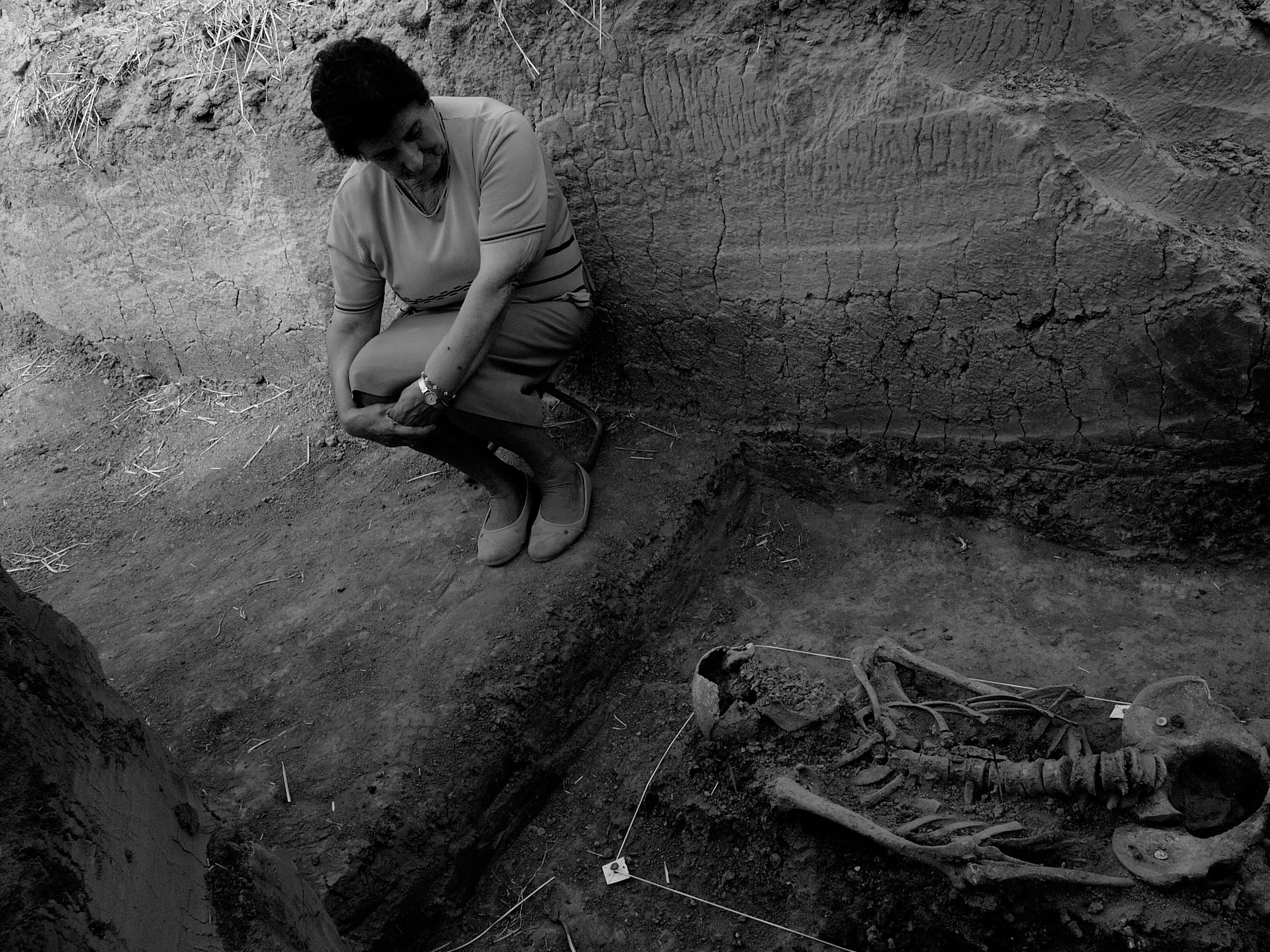 Berlangas de Roa (Burgos), 2004. Exhumation of the remains of five inhabitants of Haza (Burgos) who were detained and assassinated in August 1936, among them the mayor of the town. The mayor's daughter sits beside her father's remains. Photo Clemente Bernad. From Desvelados.