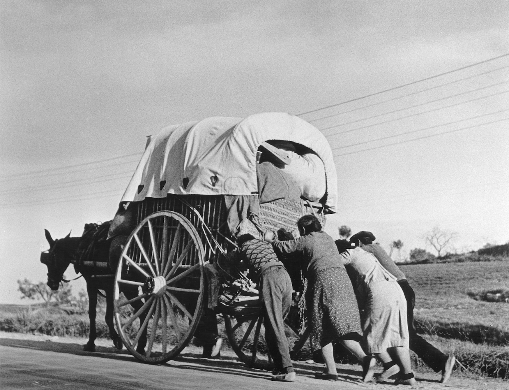 Robert Capa. Civilians from the threatened town of Tarragona pushing their wagon on their way to seek refuge in Barcelona, before that city itself had to be evacuated, January 15, 1939. © International Center of Photography/Magnum Photos.